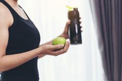 Kobieta w sprawność fizyczna kostiumu trzyma jabłka - zieleń i czerwień uzdrowiciel obraz royalty free