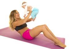 Kobieta w sprawność fizyczna ubioru chrupnięciach z dzieckiem Fotografia Royalty Free