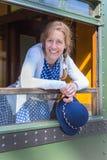 Kobieta w staromodnym odzieżowym mienie kapeluszu w taborowym okno obrazy royalty free