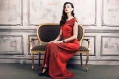 Kobieta w sukni wieczorowej na rocznika krześle Fotografia Stock