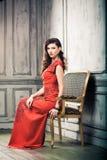Kobieta w sukni wieczorowej na rocznika krześle Zdjęcie Stock