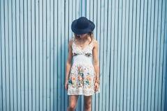 Kobieta w sukni z kapeluszowym outside błękita ogrodzeniem obraz stock