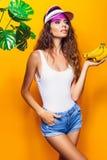 Kobieta w swimsuit i błękicie zwiera banana odizolowywających nad żółtym tłem pozować i obraz royalty free