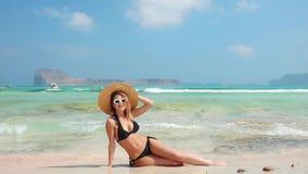 Kobieta w swimsuit relaksującym obsiadaniu na plaży zbiory