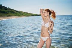 Kobieta w swimsuit trzyma ogon w ręce na dennym wybrzeżu, upał Fotografia Stock