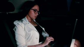 Kobieta w taxi - kobieta pracuje przy laptopem w samochodzie przy nocą zdjęcie wideo