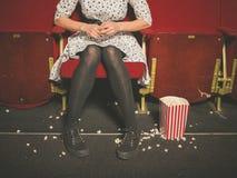 Kobieta w teatrze z popkornem na podłoga Zdjęcia Stock