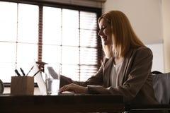 Kobieta w wózku inwalidzkim pracuje z laptopem przy stołem zdjęcia stock