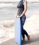 Kobieta w wetsuit i dopłynięcia deskowej pozyci oceanem Zdjęcia Stock