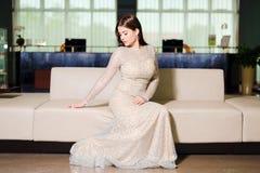 Kobieta w wieczór sukni pozuje na kanapie zdjęcia royalty free