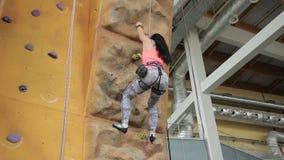 Kobieta w wyposażeniu z trudem wspina się up sztuczną skały ścianę zbiory wideo