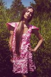 Kobieta w wysokiej trawie w różowej płatek sukni Obraz Stock