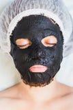Kobieta w zdroju salonie z czarną borowinową twarzy maską Obrazy Royalty Free