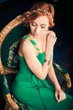 Kobieta w zielonej sukni wieczorowej na rocznika krześle Zdjęcie Stock