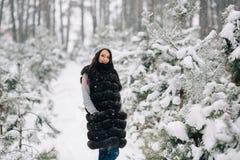 Kobieta w zimy kamizelki futerkowym odprowadzeniu w zima lesie Fotografia Royalty Free