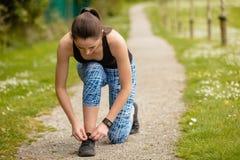 Kobieta wiąże but koronki w parku zdjęcia stock