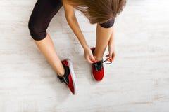 Kobieta wiąże w górę koronki na sportów butów odgórnym widoku Obraz Stock