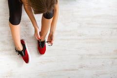 Kobieta wiąże w górę koronki na sportów butów odgórnym widoku Obrazy Royalty Free