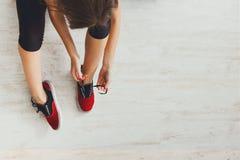 Kobieta wiąże w górę koronki na sportów butów odgórnym widoku Fotografia Royalty Free