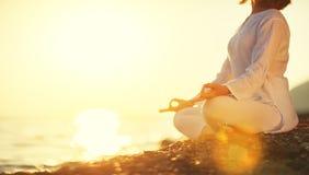 Kobieta ćwiczy joga i medytuje w lotosowej pozyci na zmierzchu b Obrazy Royalty Free