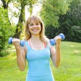 Kobieta ćwiczy z dumbbells Zdjęcia Royalty Free