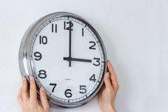 Kobieta wiesza srebnego zegar na białej ścianie zdjęcie stock