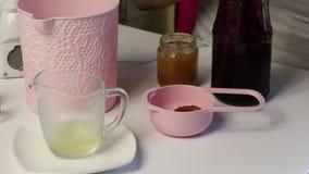 Kobieta wkłada dżem do łyżeczki miarowej Do przygotowania pianki Obok tabeli są inne składniki i narzędzia do zbiory