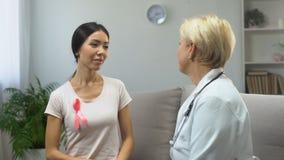 Kobieta wolontariusz jest ubranym różowego faborek opowiada fabrykować, informacja w klinice zbiory wideo