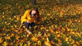 Kobieta wp8lywy od zmielonych jaskrawych spadać liści, piękna żółta wiązka zbiory wideo