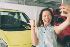 Kobieta wp8lywy selfie w nowym samochodzie przy sala wystawową zdjęcie royalty free