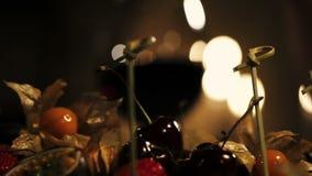 Kobieta wp8lywy wiśnia od talerza z owoc w restauraci dinner romantyczny zbiory