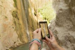 Kobieta wręcza brać fotografię siklawa z smartphone Zdjęcie Stock