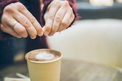 Kobieta wręcza dolewania suger latte filiżanka Zdjęcia Stock