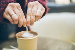 Kobieta wręcza dolewania suger latte filiżanka Obraz Stock