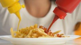 Kobieta wręcza dolewanie ketchup i musztardy w francuskich dłoniaki, ekstra kaloria posiłek zdjęcie wideo