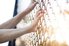 Kobieta wręcza dotykać metalu ogrodzenia drut fotografia royalty free