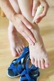 Kobieta wręcza dotykać nagiego f i creaming boli i nabrzmiewa zdjęcia stock