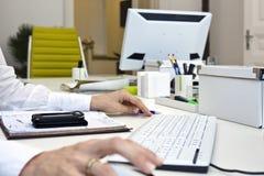 Kobieta wręcza działanie przy biurowym biurkiem Fotografia Stock