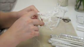 Kobieta wręcza igielnych szy białych koraliki dla włosianego akcesorium zbiory
