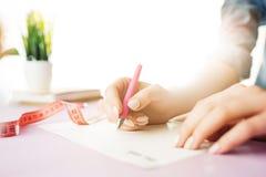 Kobieta wręcza mienia pióro Modny różowy biurko Obrazy Royalty Free