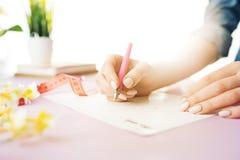 Kobieta wręcza mienia pióro Modny różowy biurko Obraz Royalty Free