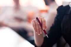 Kobieta wręcza mienia pióro na biznesowym spotkaniu Zdjęcia Stock