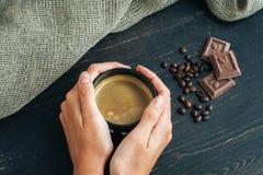 Kobieta wręcza mienie kubek gorąca kawa, stoi na drewnianym stole z czekoladą, kawowymi fasolami i parciakiem, Zdjęcie Royalty Free