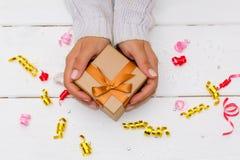 Kobieta wręcza mienie prezent na białym drewnianym stole Zdjęcia Stock