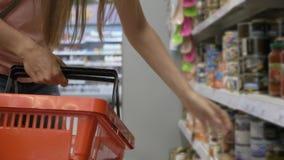 Kobieta wręcza mienie zakupy kosz i stawia towary od półek zdjęcie wideo