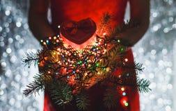 Kobieta wręcza mieniu Bożenarodzeniowego prezent, gałąź jedlinowy drzewo i Stubarwne lekkie dekoracje na ciemnym wakacyjnym tle, Obrazy Royalty Free