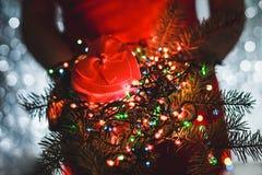 Kobieta wręcza mieniu Bożenarodzeniowego prezent, gałąź jedlinowy drzewo i Stubarwne lekkie dekoracje na ciemnym wakacyjnym tle, Obrazy Stock