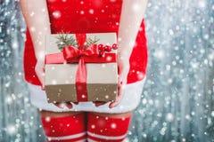 Kobieta wręcza mieniu Bożenarodzeniowego prezenta pudełko z czerwonym faborkiem, gałąź jedlinowy drzewo na błyszczącym xmas tle W Zdjęcia Royalty Free