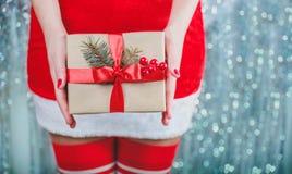 Kobieta wręcza mieniu Bożenarodzeniowego prezenta pudełko z czerwonym faborkiem, gałąź jedlinowy drzewo na błyszczącym xmas tle W Obraz Royalty Free