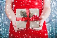 Kobieta wręcza mieniu Bożenarodzeniowego prezenta pudełko z czerwonym faborkiem, gałąź jedlinowy drzewo na błyszczącym xmas tle Fotografia Stock